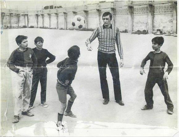 foto di Gigi Riva che gioca a pallone con alcuni bambini nel quartiere Marina